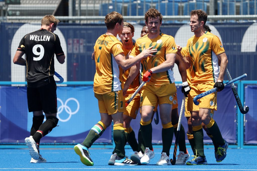 TOKYO, JAPAN - JULY 29: Matthew Guise-Brown of Team South Africa celebrates scoring the first goal with Timothy Drummond and teammates while Niklas Wellen of Team Germany walks away during the Men's Preliminary Pool B match between South Africa and Germany on day six of the Tokyo 2020 Olympic Games at Oi Hockey Stadium on July 29, 2021 in Tokyo, Japan. (Photo by Buda Mendes/Getty Images)